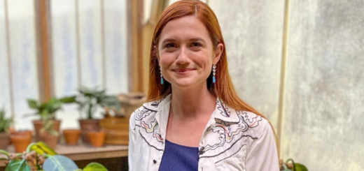 """Bonnie Wright (Ginny Weasley) is photographed by Rosy Cordero for """"Entertainment Weekly"""" at Warner Bros. Studio Tour Hollywood in June 2021. She is pictured smiling in a replica Herbology greenhouse."""