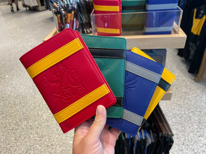 Hogwarts House passport covers are pictured as photographed by WDW News Today at Universal Orlando Resort. Each passport cover features an accent color in addition to the main color.