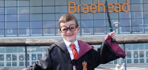 A child in Harry Potter glasses and robes is waving a wand in front of the Braehead shopping mall.