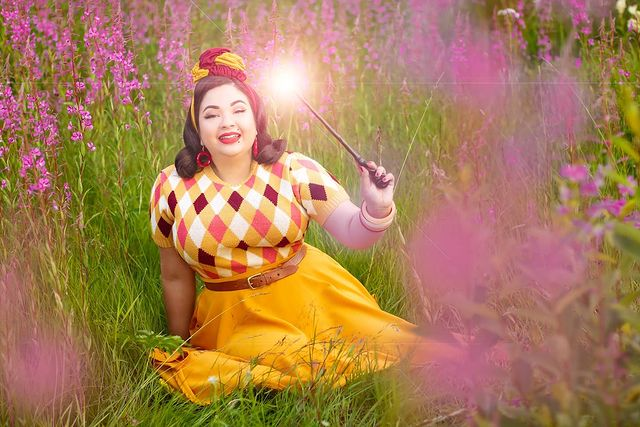 A HufflePuff fan poses for a photo, holding a wand in a beautiful field of flowers