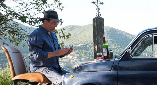 Ciaran Hinds is resting by the road by his old fashionaed car with a lovely background of the south of France.