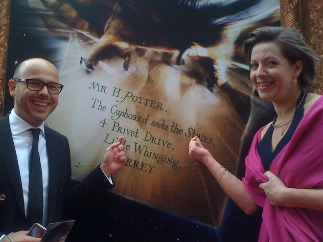 Eduardo Lima and Miraphora Mina are pictured in front of a poster of Harry's Hogwarts letter.