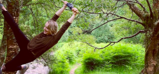 Evanna Lynch swings on a rope swing hanging from a tree.