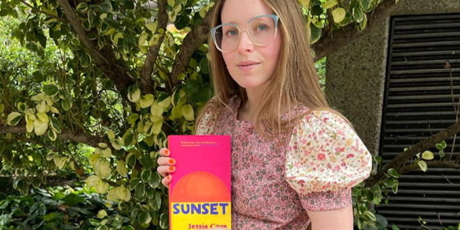 """Jessie Cave (Lavender Brown) is pictured holding a copy of her debut novel, """"Sunset,"""" available now."""