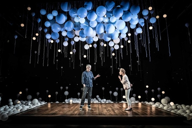 A theatre stage is pictured with Peter Capaldi and Zoe Wanamaker acting a scene facing each other. There are a lot of white, luminous balloons around the square stage bit they are standing on as well as floating overhead.
