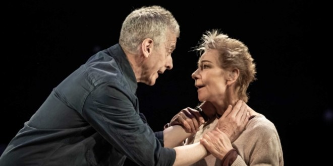 Peter Capaldi and Zoe Wanamaker are in an intense scene, arms locked, smiling at each other.