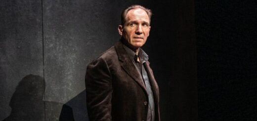 Ralph Fiennes is posing against a dark set in performance of Four Quartets on stage.