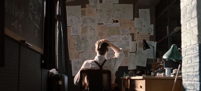 """A still from """"The Imitation Game"""" picturing Benedict Cumberbatch as Alan Turing face a wall of sketches and design (designed by MinaLima)."""