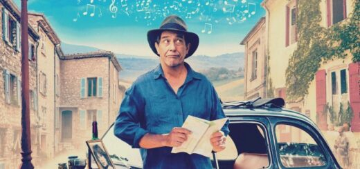 Ciaran Hinds as the Man in the Hat with a car and a French small town bacdrop on the movie poster for The Man in the Hat.