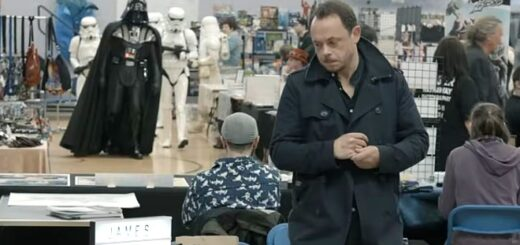 James Payton is standing in a black coat behind a desk at a convention. There is a Darth Vader cosplayer in the background.