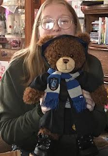 Elise holding up her Ravenclaw bear.