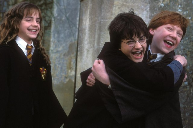 Harry, Ron and Hermione are hugging and laughing