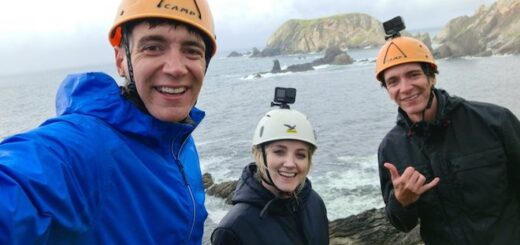 Oliver Phelps, Evanna Lynch, and James Phelps are wearing hard hats and posing in front of the Irish coastline.