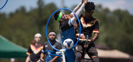 There is a chaser from New York Titans who threw a quaffle through the hoops. A keeper from Austin Outlaws is trying to stop him. Chaser from New York Titans and chaser from Austin Outlaws are watching them in the background.
