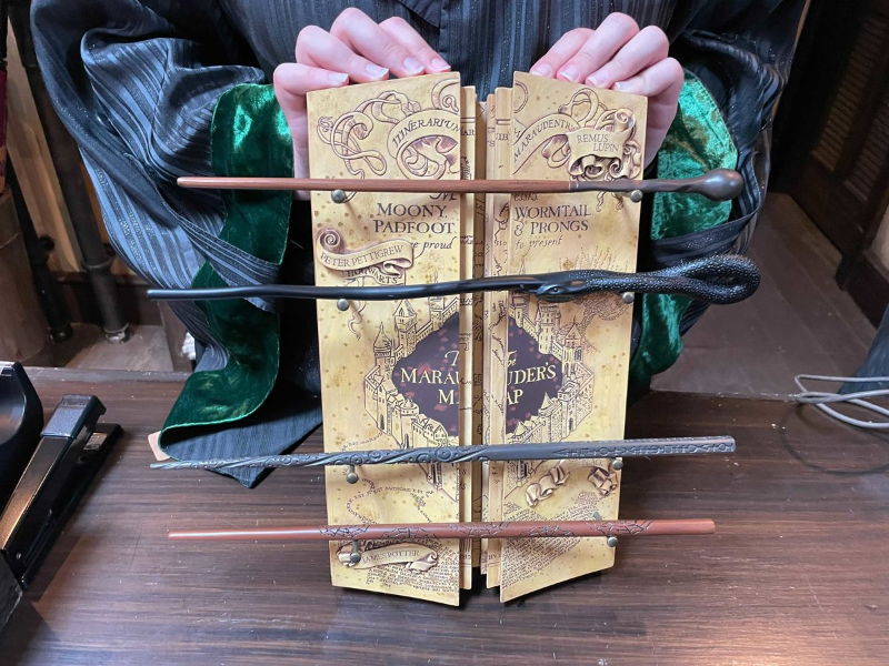 The Marauder's Map Wand Collection at Universal Orlando Resort is pictured in a photograph from WDW News Today. It features the wands of the four Marauders on a decorative Marauder's Map stand.