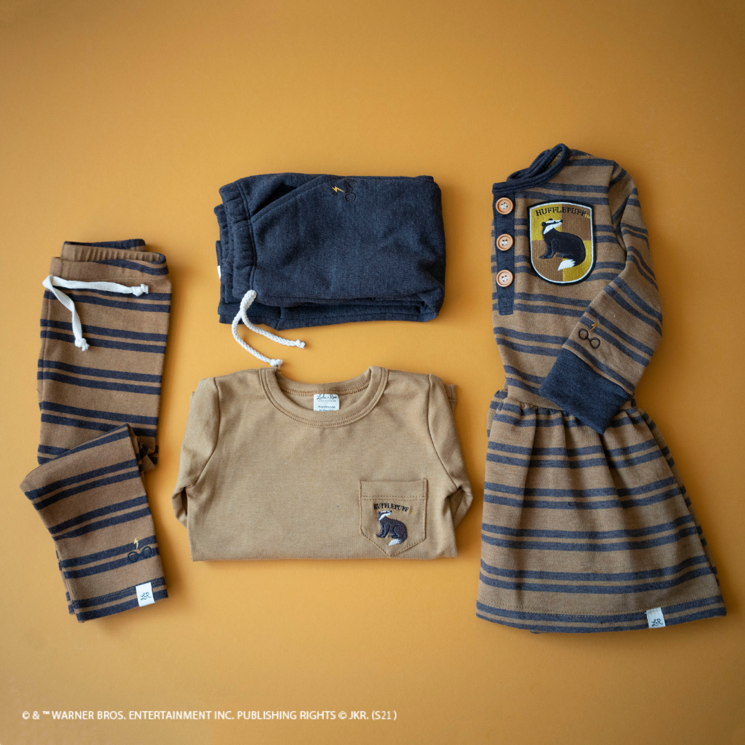 The Harry Potter X Lulu and Roo collection features a variety of clothing, including dresses, in the four Hogwarts Houses colors and mascots.